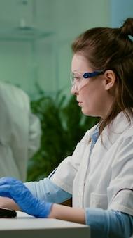 Ricercatore chimico che analizza il campione di prova messo al microscopio per esperimenti farmaceutici