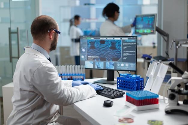코로나바이러스 치료에서 일하는 화학자 연구원 의사 타이핑 바이러스 전문 지식
