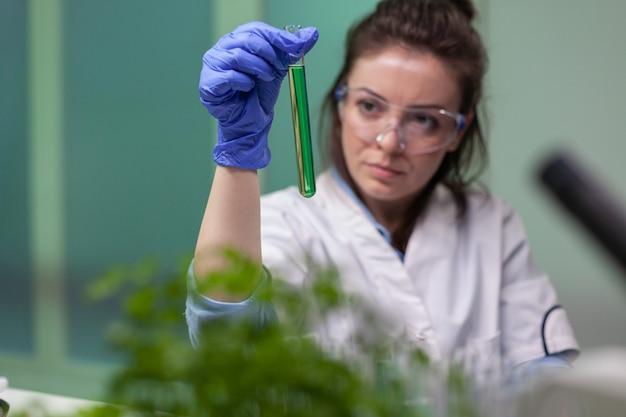 Dna液体で試験管を保持している化学者研究者の女性