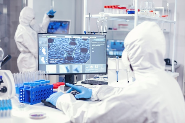 Chemist sits at his workplace in laboratory analyze coronavirus on computer dressed in ppe
