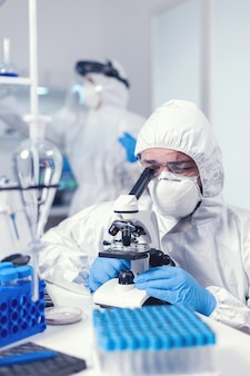 Chemist with face mask and ppe developing vaccine for covid looking through microscope. scientist in protective suit sitting at workplace using modern medical technology during global epidemic.