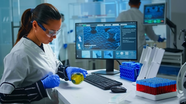 Chemist with protection glass examining various bacteria holding petri dish in laboratory typing on pc. doctors analysing vaccine evolution using high tech researching diagnosis against covid19 virus.