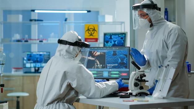 장비를 갖춘 실험실에서 바이러스 개발을 확인하는 pc에 타이핑하는 ppe 정장을 입은 화학자. 다양한 박테리아, 조직 및 혈액 샘플로 작업하는 팀 의사, 항생제에 대한 제약 연구