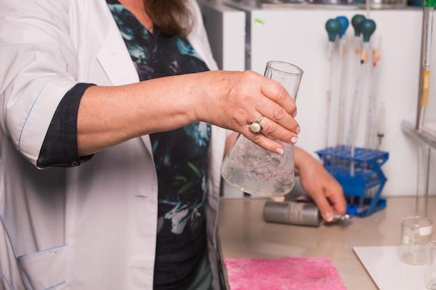 化学者は研究室で働いています。水質をテストするラボアシスタントのクローズアップ