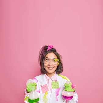 Chemist works in science laboratory conducts chemical experiment holds glass flasks concentrated with happy expression above isolated on pink