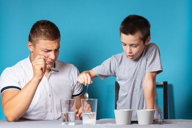 화학 교육 및 연구 개념입니다. 소년과 그의 아버지의 클로즈업, 과학자들은 집에서 실험을 위해 화학 원소가 든 병에 물을 붓습니다