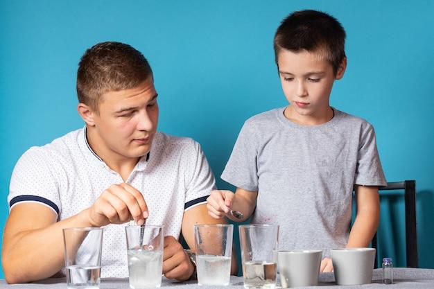 화학 교육 및 연구 개념입니다. 소년과 그의 아버지의 클로즈업, 과학자들은 집에서 실험을 위해 화학 원소가 든 유리에 물을 붓습니다