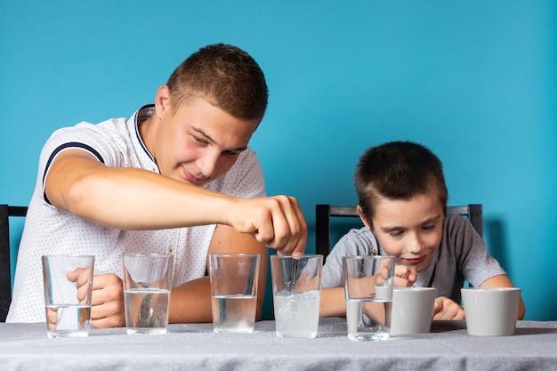 화학 교육 및 연구 개념입니다. 아빠와 그녀의 아들은 집에서 실험하기 위해 계량 숟가락을 화학 원소가 담긴 용기에 저어줍니다