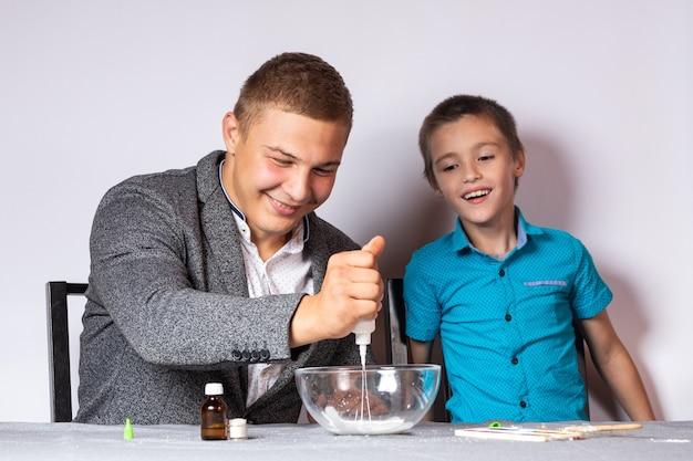 화학 교육 및 훈련 개념입니다. 집에서 화학 실험을 하는 한 소년과 그의 아빠의 클로즈업, 접착제, 사붕산나트륨, 염료로 점액 만들기