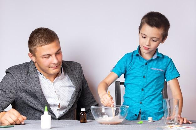 Концепция образования и обучения химии. крупный план мальчика и его отца, которые проводят домашний химический эксперимент, делая слизь из клея, тетрабората натрия и красителей.