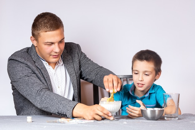 化学教育とトレーニングの概念。でんぷんと水から非ニュートン液体を作る、家庭での体験をしている少年と彼のお父さんのクローズアップ