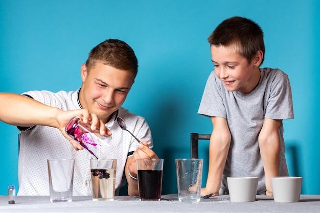 Концепция образования и обучения химии. крупный план мальчика и его папы, ученые заливают перманганат калия в пробирку для эксперимента с изменением цвета, эксперименты в домашних условиях