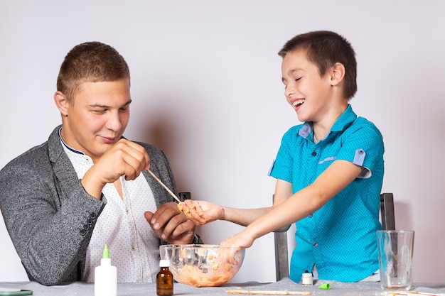 Chemistry education and training concept. close-up of a boy and his dad doing a home chemical experiment, making slime from glue, sodium tetraborate and dyes