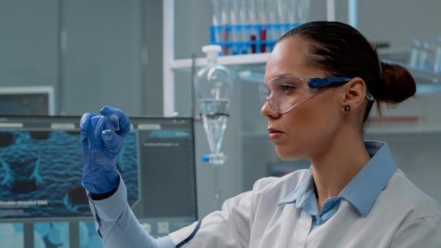 유리에 혈액 샘플을 분석하는 화학 전문가