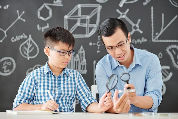 Учитель химии и школьник смотрят внутрь чашки петри через увеличительное стекло