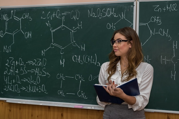 Chemistry teacher in front of a chalkboard explain a lesson.  interesting and fascinating. explore science.