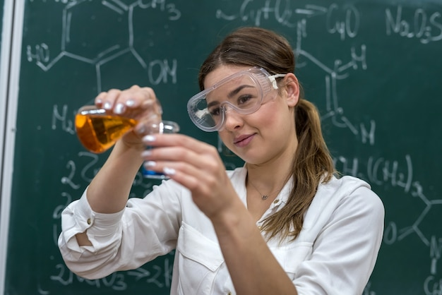 Учитель химии держит фляжку с оранжевой жидкостью и проводит в классе научный эксперимент. наука