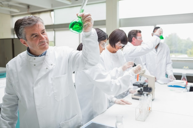 Chemists doing research on green liquid