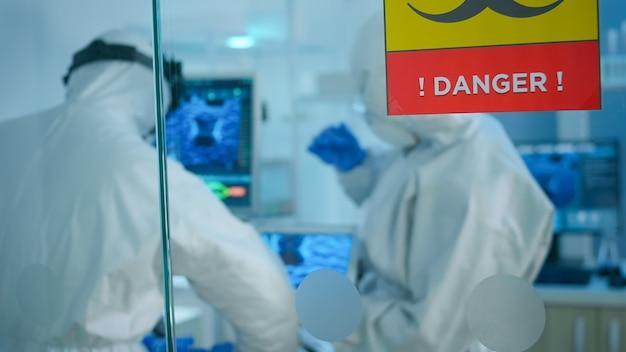 실험실의 위험 구역에서 일하는 유리 벽 뒤에 서있는 태블릿을 사용하여 백신을 개발하려는 작업복의 화학자들