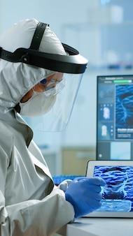 Химики в комбинезоне работают над разработкой вакцины с помощью таблеток в оборудованной лаборатории. ученые изучают эволюцию вируса с помощью высоких технологий для научных исследований разработки лечения против covid19