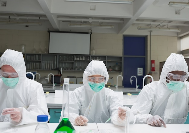 Chemists in protective suits adding liquid to petri dishes