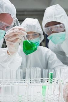 Chemists in protective suits looking at green liquid in beaker