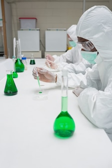 Chemists in protective suits working with green chemical