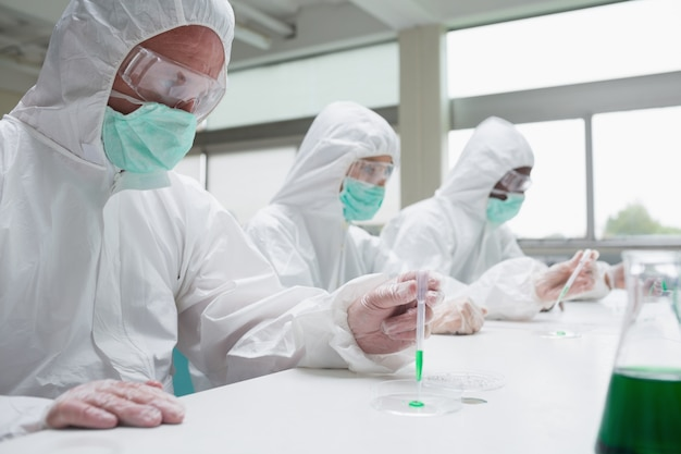 Chemists in protective suits working