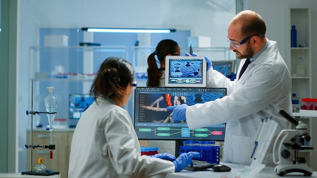 화학자들은 실험실에서 토론하는 태블릿의 dna 정보를 비교하는 바이러스 진화에 대해 걱정했습니다. covid19 바이러스에 대한 첨단 연구 치료법을 사용하여 백신 개발을 조사하는 물건