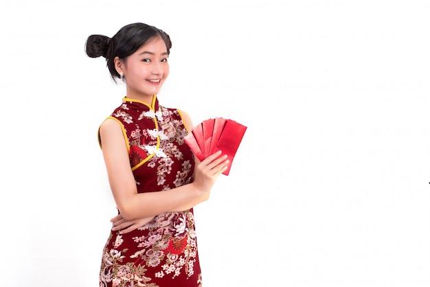 Cheongsamを着てパケットを保持している若いアジアの美人の女性