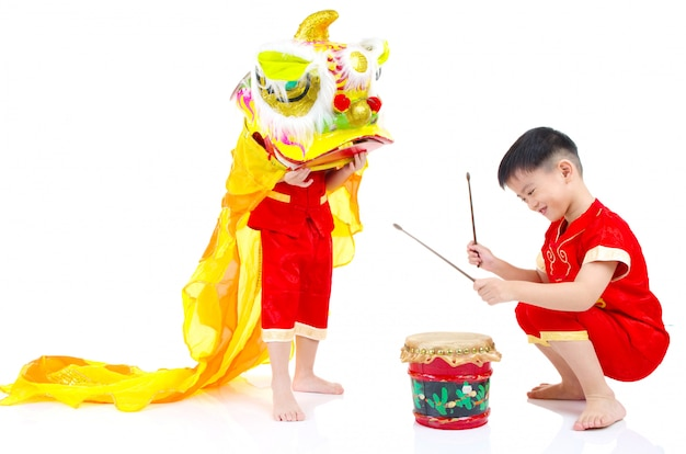 Азиатские китайские дети в традиционном китайском cheongsam празднуя китайский новый год, изолированные на белом фоне.