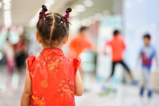 Маленькая девочка с красным cheongsam. китайский новый год