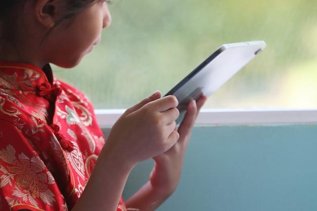 Азиатская милая девушка носить cheongsam она ищет технологии развлечений