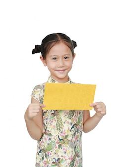 Красивейшая азиатская маленькая девочка в традиционном cheongsam с держать конверт золота для счастливого китайского нового года изолировала