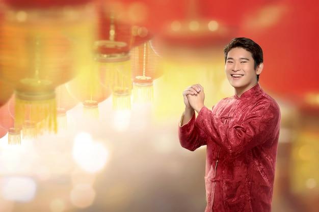 Молодой китайский человек в костюме cheongsam стоя с висящими фонариками