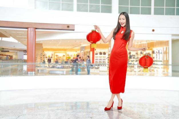 Азиатская китаянка в платье cheongsam держит китайский фонарь
