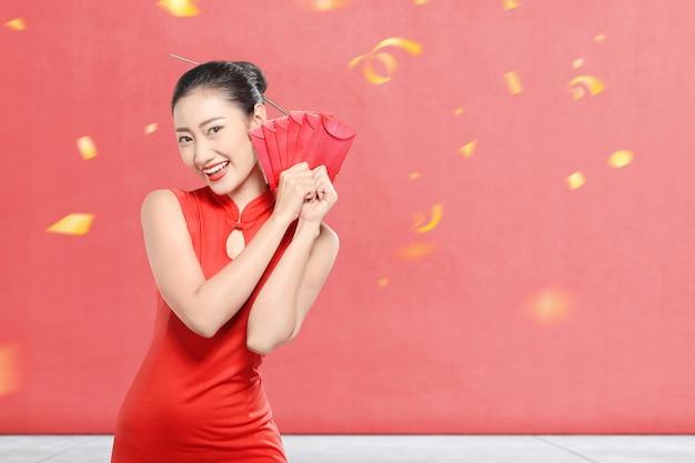 Азиатская китаянка в платье cheongsam держит красные конверты