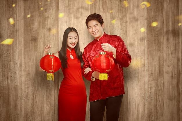 Азиатская китайская пара в платье cheongsam держит китайский фонарь