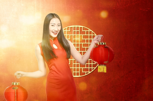 Азиатская женщина в платье cheongsam держит китайский фонарь