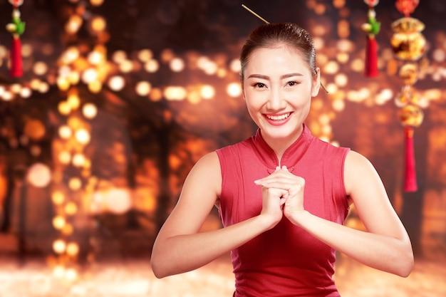 Азиатская женщина в платье cheongsam с жестом поздравления
