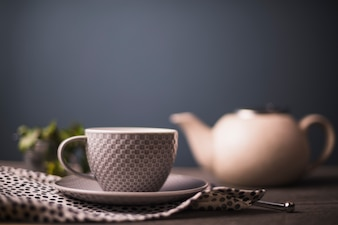 Chequered pattern tea cup on polka dotted textile on table