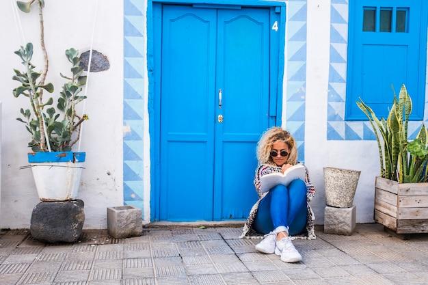 陽気でリラックスした美しい女性が床の本を読んで通りのカラフルな青い家の外に座って