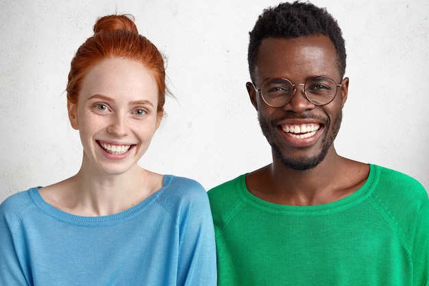 Cherful freckled ginger woman and male stand closely, show white teeth, rejoice meeting, isolated over concrete studio wall