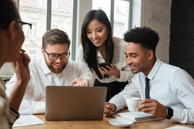 Cherful позитивные молодые коллеги, используя портативный компьютер.