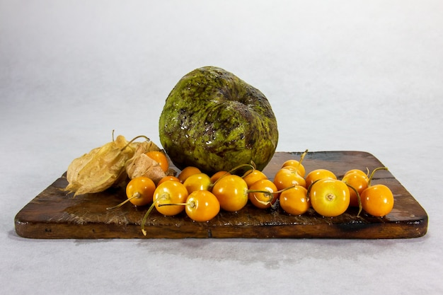Cherimoya y uchuva aguaymanto uvillaエキゾチックなペルーのラテンアメリカの果物は、茶色の木の板と影の白い背景の上に座っています