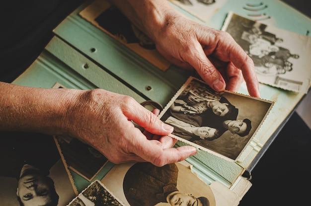 Черкассы / украина - 12 декабря 2019 г .: женские руки держатся за старые фото ее родственников