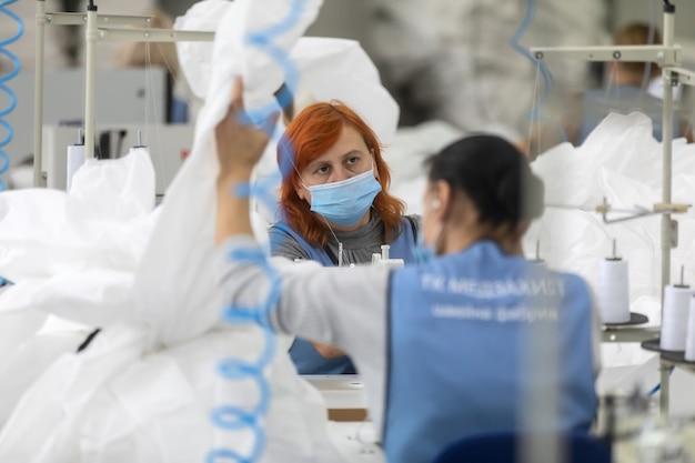 체르니 기프, 우크라이나-2020 년 10 월 6 일 : 우크라이나 체르니 기브에있는 봉제 공장 tk 스타일에서 코로나 19 유행병 발생시 의료진과 의사를위한 보호 복 재봉