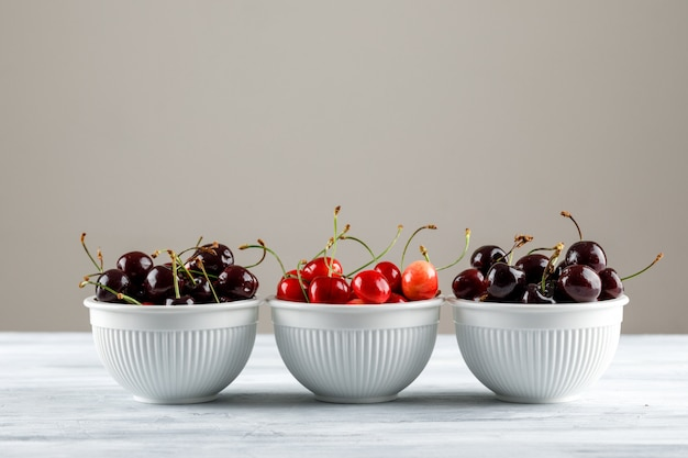 Cherries in bowls side view on grey gradient and grunge surface