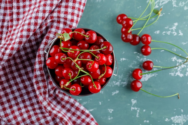 Cherries in a bucket flat lay on plaster and kitchen towel