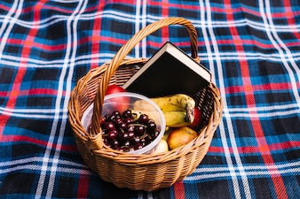 Cherries; fruits and book in the basket on blanket